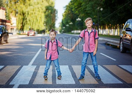 Kids with backpack walking holding on warm day on the road