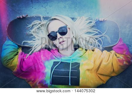 Blond skater girl laying down with board