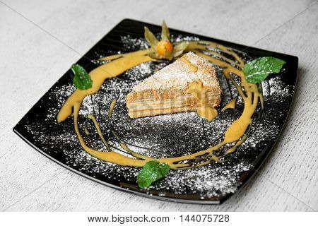 Delicious piece of cake on black plate