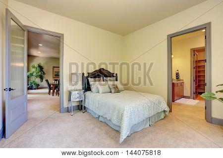 Elegant Single Carved Wooden Bed. Open Door To Bathroom.