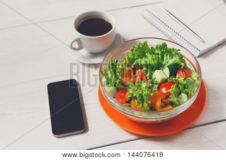 Healthy business lunch in office, vegetable salad bowl on white wooden desk. Salad bowl, coffee, mobile phone and notepad with pen flat lay. Snack at break time