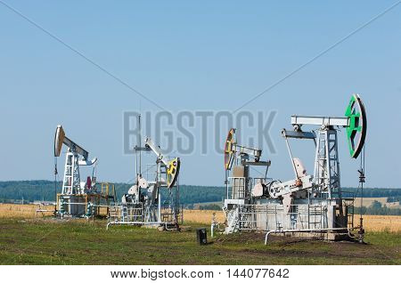 Oil pumps. Oil rocking chair. Oil industry equipment. Oil rocking chair closeup. Oil rocking chair on a background of blue sky. The pumping unit as the oil pump installed on a well.