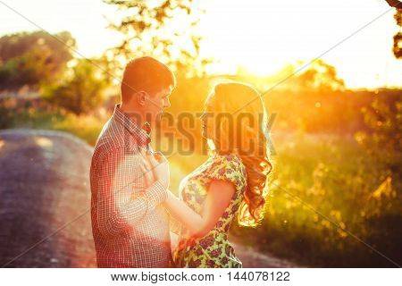 A loving couple looking at each other in the last rays of the sun in a field near the road.