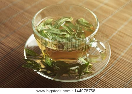 Cup of sage tea on wicker mat background