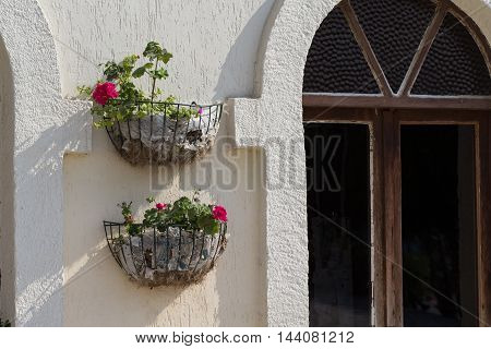 large pots of geraniums on a white stone wall