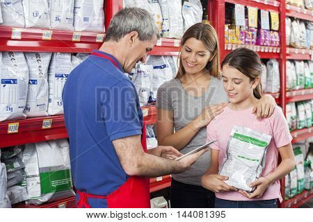 Salesman Using Tablet Computer While Assisting Family In Pet Sto