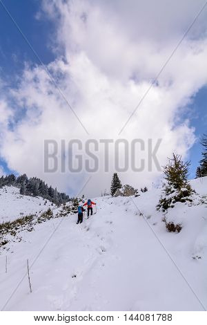 Panoramic view with two skiers and covered trees. Vertical view with winter landscape of snow-covered trees on mountains and beautiful sky.