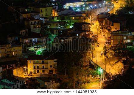 Lighted street at night in Italy. Panoramic view with lighted street at night cars and villas.