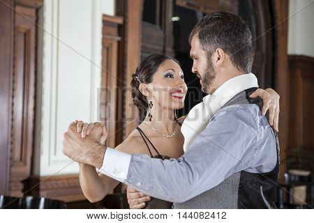 Happy Man And Woman Performing Tango In Restaurant
