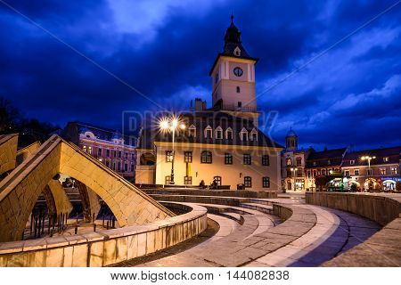 Brasov Romania - February 23: The Council Square on February 23 2016 in Brasov Romania. Panoramic view with the buildings beautiful blue sky in evening public lights and fountain.