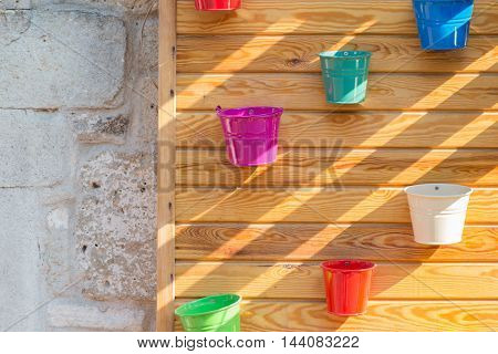 tin brightly colored flower pots on wooden wall