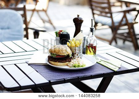 American burger, spring salad and french  fries on the wood table at the restaurant cafe bistro pizzeria terrace.