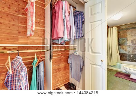 Close-up View Of Clothes And Shirts On Wooden Hangars In A Closet.