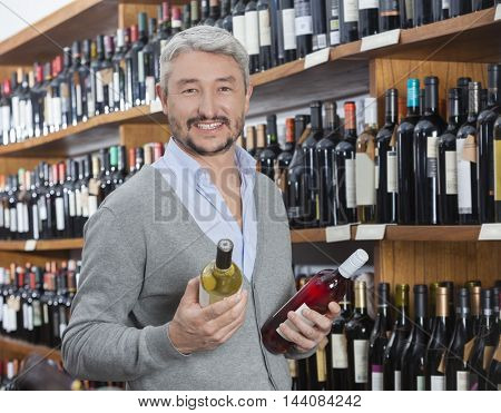 Customer Holding Red And White Wine Bottles In Store