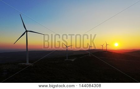 Aerial view of five electricity generating windmills at sunset
