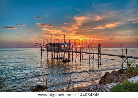 CHIETI, ABRUZZO, ITALY - SEPTEMBER 14: Adriatic sea coast at sunrise with an ancient fishing hut trabocco, the typical mediterranean wooden pilework. Photo taken on September 14, 2016 in Chieti, Abruzzo, Italy