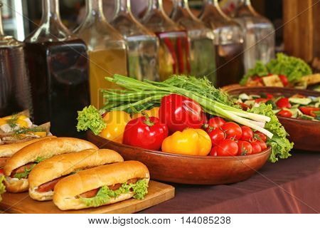 Fresh vegetables, different drinks and sandwiches on counter