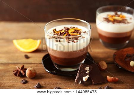 Layered desserts with decoration on wooden table