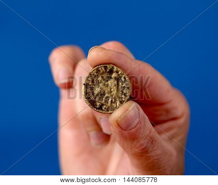 picture of a Fingers hold ancient coin