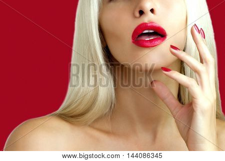 The face of a beautiful blonde with red lipstick and red nail polish on a red background