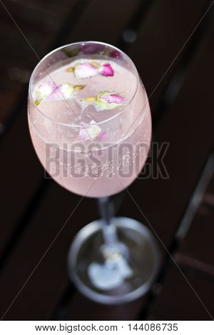 Glass of lemonade on wood.Glass of water with rose flowers and ice