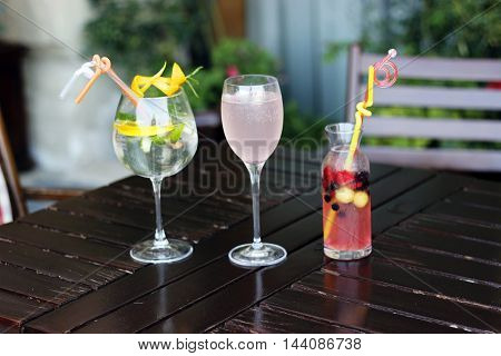 Glasses of lemonade on wood table. Three glasses of water with fresh lemon, ice, fruit, rose,berry and mint