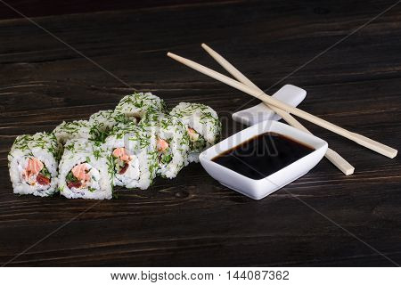 Sushi Roll On Wooden Background . They Were 8 Pieces .lay Next To Sticks And Is Dishes With Sauce.