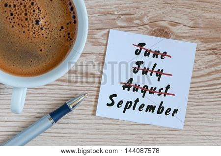 September beginning and summer end concept written at notepad with morning cup of coffee. Striked June, July, August.