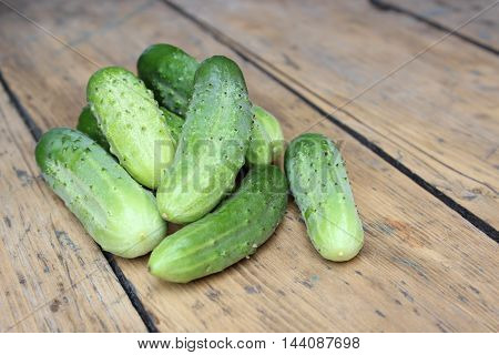 Scattered green cucumbers on background of wooden planks