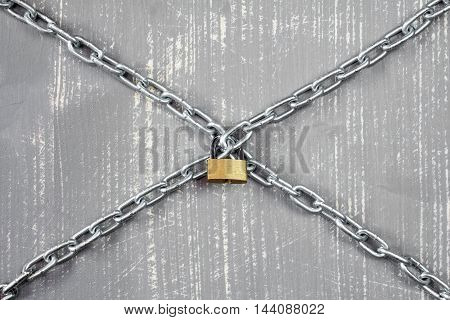 Steel chains and padlock on the grey wooden background