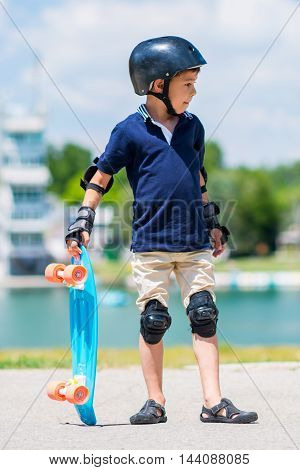 Cool little kid with skateboard, toned image,