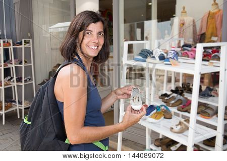 Pregnancy shopping. Portrait of pregnant woman choosing newborn clothes at baby shop store