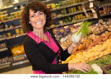 Confident Brunette Woman Buying Vegetable On Stall At The Market