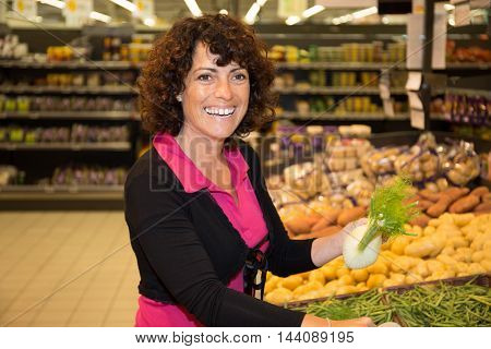 Smiling Brunette woman buying vegetable on stall at the market