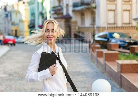 Happy smiling business woman with book in white shirt on the street outdoor