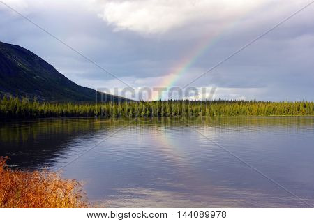 Rainbow after rain over the northern lake surrounded by mountains