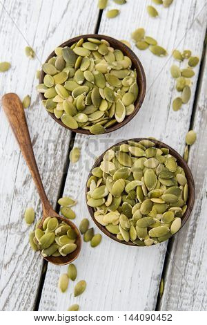 fresh pumpkin seeds on a white wood background rustic style selective focus