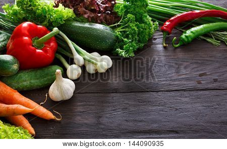 Border of fresh organic vegetables on wood background. Healthy natural food on rustic wooden table with copy space. Tomato, lettuce, carrot, pepper, zucchini and other cooking ingredients top view
