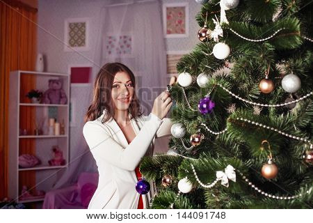 beautiful girl decorates the Christmas tree. The concept of New Year and Merry Christmas