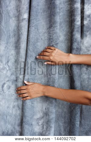 Close up photo of girl's hands over grey cloth background. From above.