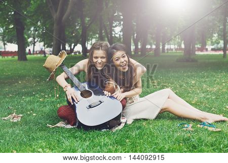 Two happy boho chic stylish girlfriends picnic in park. Young girls outdoors in park on the grass at summer sunny day. Women listen music in earphones together, sit at plaid with guitar