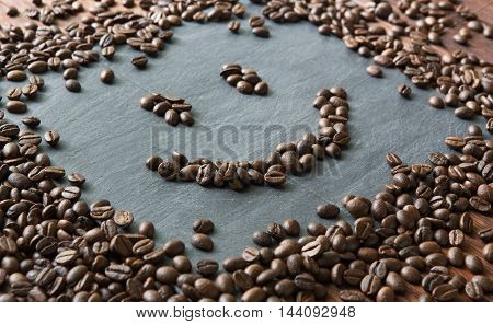 Smiley face from coffee beans. Heap of roasted coffee bean on grey stone surface texture. Coffee shop or cafe background. Natural stone and smiling face from beans. Soft color toning