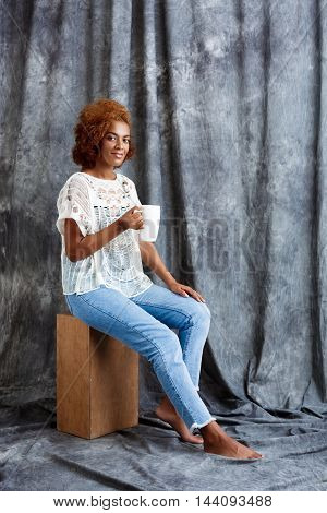 Young beautiful african girl sitting at wooden box, smiling, holding cup over grey cloth background. Copy space.
