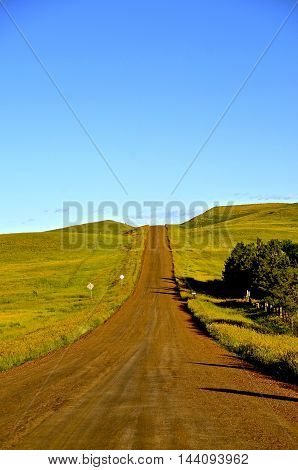 Rural country road covered with scoria rock leads uphill in western North Dakota