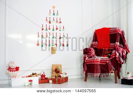 Christmas decorations. a comfortable armchair with a plaid gifts Christmas Tree Christmas cookies laid out on a white wall