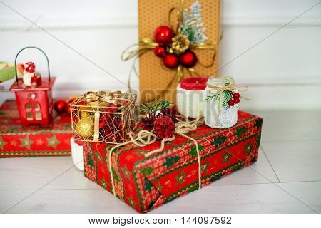 Christmas presents in red paper decorated with cones balls and branches snow