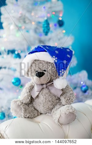 toy bear in a Christmas cap sits under the Christmas tree