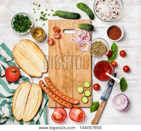 Ingredients for making hot-dogs. Sausages, fresh vegetables, ketchup, mustard, bread and spices with chopping board in center over white painted wooden background, top view, copy space