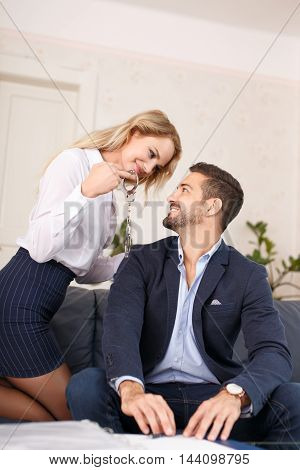 Sexy blonde businesswoman holding handcuffs to rich young businessman seduction