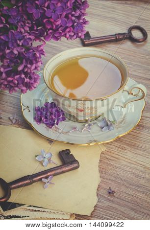 summer cup of tea with lilac flowers and vintage photos, retro toned